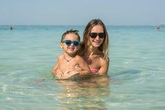 Familia sonriente feliz que se divierte en las islas blancas tropicales de Maldivas de la playa Madre e hijo lindo Emociones huma Fotografía de archivo