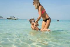 Familia sonriente feliz que se divierte en las islas blancas tropicales de Maldivas de la playa Madre e hijo lindo Emociones huma Foto de archivo libre de regalías