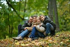 Familia sonriente feliz que se sienta en las hojas Foto de archivo