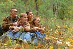 Familia sonriente feliz que se sienta en las hojas Imágenes de archivo libres de regalías