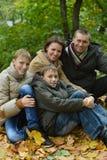 Familia sonriente feliz que se sienta en las hojas Imagen de archivo