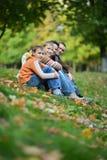 Familia sonriente feliz que se sienta en las hojas Fotos de archivo