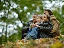 Familia sonriente feliz que se sienta en las hojas Imagenes de archivo