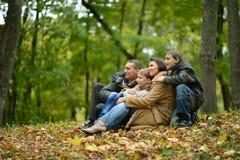 Familia sonriente feliz que se sienta en las hojas Fotografía de archivo libre de regalías