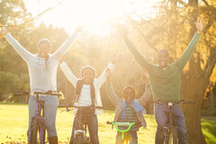Familia sonriente joven que hace un paseo de la bici con los brazos aumentados Imagen de archivo libre de regalías