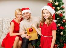 Familia sonriente que adorna el árbol de navidad Foto de archivo
