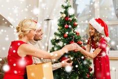 Familia sonriente que adorna el árbol de navidad Imágenes de archivo libres de regalías