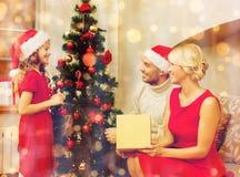 Familia sonriente que adorna el árbol de navidad Fotografía de archivo libre de regalías