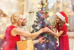 Familia sonriente que adorna el árbol de navidad Imagen de archivo