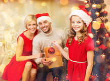 Familia sonriente que adorna el árbol de navidad Imagen de archivo libre de regalías