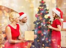Familia sonriente que adorna el árbol de navidad Imagenes de archivo