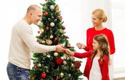 Familia sonriente que adorna el árbol de navidad en casa Foto de archivo libre de regalías