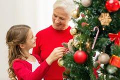 Familia sonriente que adorna el árbol de navidad en casa Imagen de archivo libre de regalías