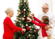 Familia sonriente que adorna el árbol de navidad en casa Fotografía de archivo libre de regalías