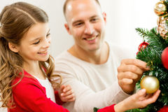 Familia sonriente que adorna el árbol de navidad en casa Imagen de archivo