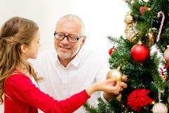Familia sonriente que adorna el árbol de navidad en casa Imágenes de archivo libres de regalías