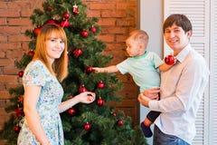 Familia sonriente que adorna un árbol de navidad en la sala de estar Fotos de archivo libres de regalías