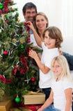 Familia sonriente que adorna un árbol de navidad Fotografía de archivo libre de regalías
