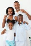 Familia sonriente que aplica sus dientes con brocha Imagen de archivo libre de regalías