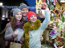 Familia sonriente que camina en el mercado de la Navidad Fotos de archivo libres de regalías