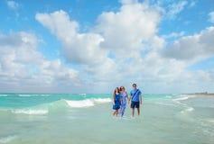 Familia sonriente que camina en la playa hermosa Fotografía de archivo libre de regalías