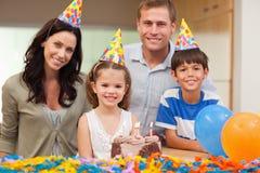 Familia sonriente que celebra cumpleaños de las hijas Fotos de archivo libres de regalías