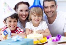 Familia sonriente que celebra un cumpleaños Foto de archivo libre de regalías