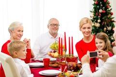 Familia sonriente que cena el día de fiesta en casa Foto de archivo libre de regalías