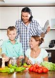 Familia sonriente que cocina verduras Imagen de archivo