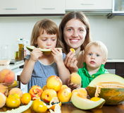 Familia sonriente que come el melón Imagenes de archivo