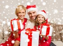 Familia sonriente que da muchas cajas de regalo Imagen de archivo libre de regalías