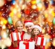 Familia sonriente que da muchas cajas de regalo Fotos de archivo libres de regalías