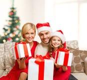 Familia sonriente que da muchas cajas de regalo Fotos de archivo