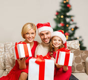 Familia sonriente que da muchas cajas de regalo Imagen de archivo