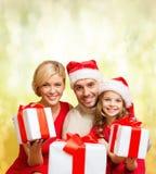 Familia sonriente que da muchas cajas de regalo Fotografía de archivo