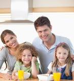 Familia sonriente que desayuna Foto de archivo