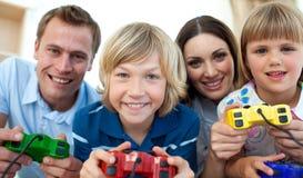 Familia sonriente que juega a los juegos video juntos Imágenes de archivo libres de regalías