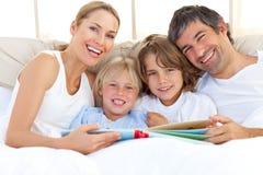 Familia sonriente que lee un libro en cama Fotografía de archivo