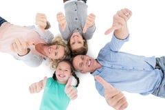 Familia sonriente que miente en el piso en un círculo que muestra los pulgares para arriba Foto de archivo libre de regalías