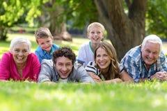 Familia sonriente que miente en la hierba imágenes de archivo libres de regalías