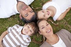 Familia sonriente que miente en un parque Fotos de archivo libres de regalías