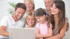 Familia sonriente que mira algo en el ordenador portátil Imagen de archivo