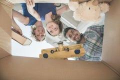Familia sonriente que mira en una caja de cartón, visión desde directamente debajo fotos de archivo