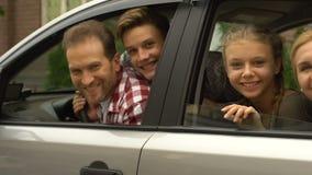 Familia sonriente que mira fuera del nuevo coche, compra muy esperada, seguro auto almacen de metraje de vídeo