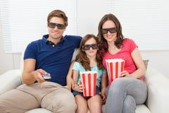 Familia sonriente que mira la película 3d en casa Imagen de archivo