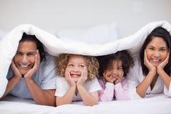 Familia sonriente que oculta bajo la manta Imagen de archivo libre de regalías