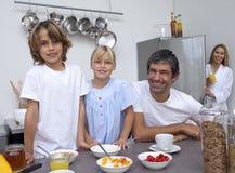 Familia sonriente que prepara el desayuno Fotografía de archivo