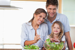 Familia sonriente que prepara una ensalada Foto de archivo libre de regalías