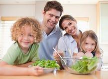 Familia sonriente que prepara una ensalada junta Imágenes de archivo libres de regalías