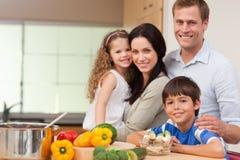 Familia sonriente que se coloca en la cocina Fotografía de archivo
